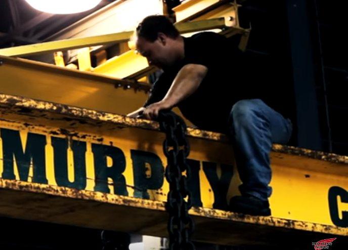 鉄鋼に乗って作業する男性