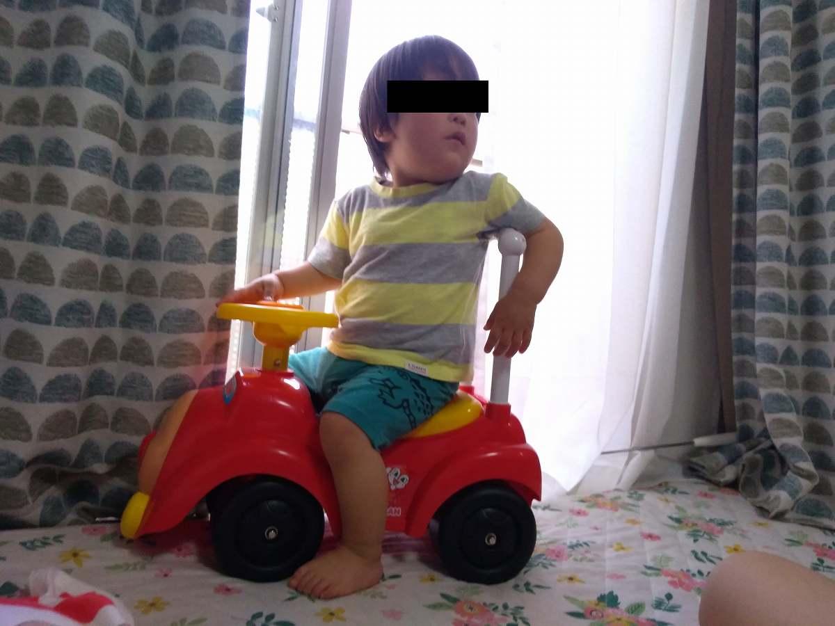 車のおもちゃに乗る子ども
